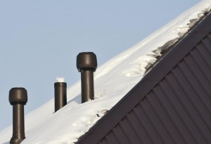 Insulated plastic ventilation pipes on the snowbounded roof